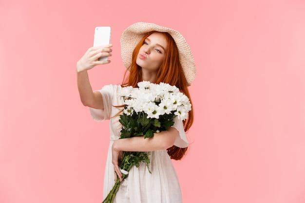 Głupiutka I śliczna, Kobieca Blogerka Robiąca Selfie Z Bukietem Kwiatów Przyniesionych Przez Chłopaka, Trzymająca Smartfon Składane Usta W Pocałunku Powietrznym, Pozująca Do Idealnego Zmysłowego Strzału, Stojąca Na Różowo Premium Zdjęcia