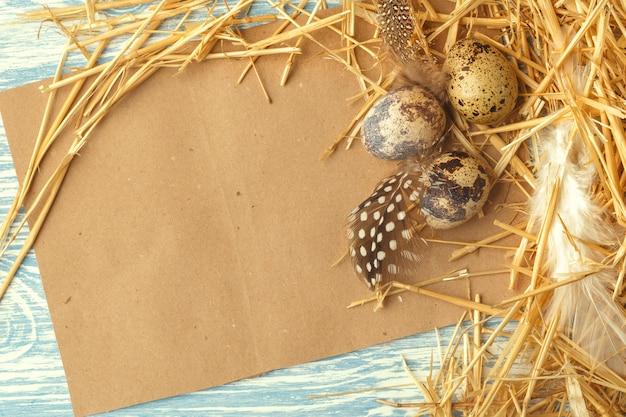Gniazduje Z Wielkanocnymi Jajkami Na Błękitnej Drewnianej Powierzchni, Odgórny Widok Z Kopii Przestrzenią Premium Zdjęcia