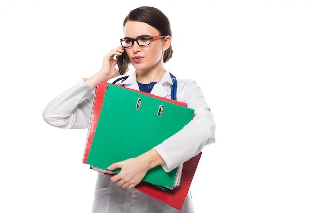 Gniewna Młodej Kobiety Lekarka Z Stetoskopu Mienia Segregatorami W Jej Rękach I Opowiadać Na Telefonie W Bielu Mundurze Premium Zdjęcia