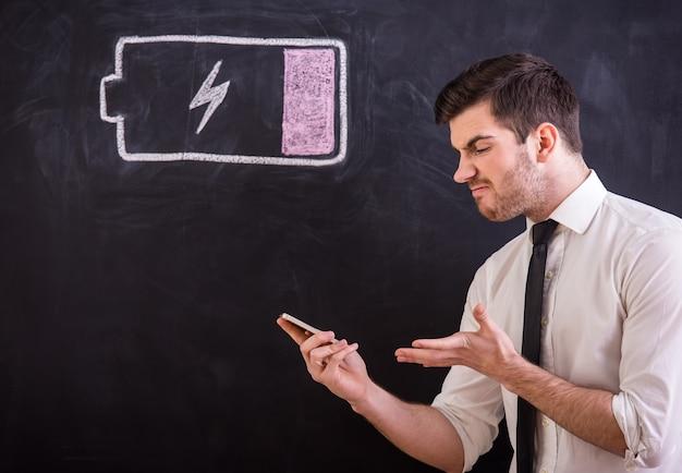 Gniewny Młody Człowiek Trzyma Jego Smartphone Z Bateryjną Niską. Premium Zdjęcia