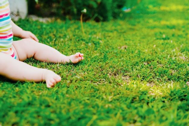 Gołe Stopy Dziecka Siedzącego Na Trawie, Z Dużą Ilością Wolnego Miejsca Na Tekst. Premium Zdjęcia