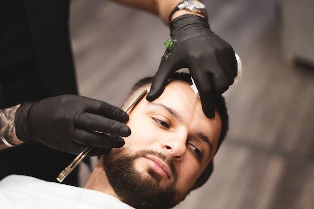 Golenie brody w zakładzie fryzjerskim niebezpieczną brzytwą. pielęgnacja brody barber shop. suszenie, strzyżenie, strzyżenie brody. selektywne ustawianie ostrości. Premium Zdjęcia