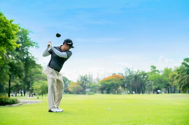Golfista uderzający golf strzelał z klubem na kursie podczas wakacji. Premium Zdjęcia