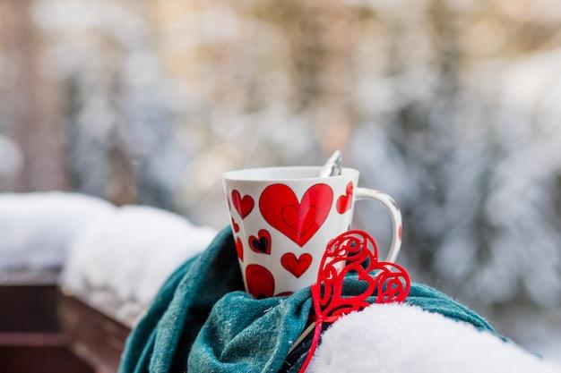 Gorąca Czekolada Lub Kawa, Czerwone Serce W Pobliżu Filiżanki, Zimowe Tło Z Nieostrym Oświetleniem. Tło Zima Lub Walentynki Premium Zdjęcia