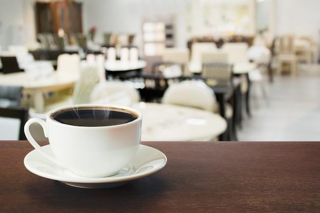 Gorąca Filiżanka Czarnej Kawy Na Blacie W Kawiarni. Wewnątrz. Premium Zdjęcia