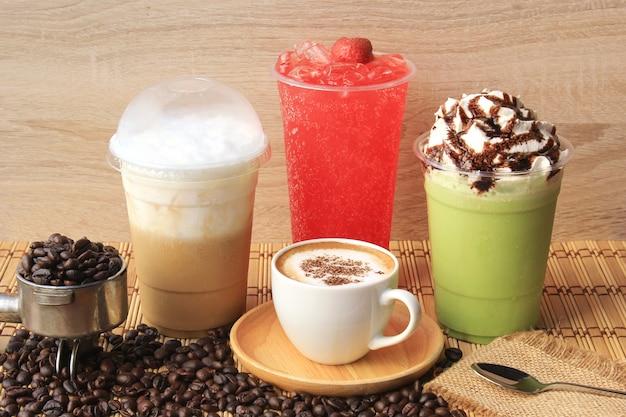 Gorąca filiżanka kawy z ziaren kawy na drewnianym stole, zimna kawa, mrożona matcha zielona herbata i soda owocowa na letni napój Premium Zdjęcia
