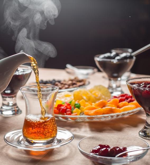 Gorąca herbata wlewa się do szklanki armudu w tradycyjnym azerbejdżańskim zestawie do herbaty Darmowe Zdjęcia
