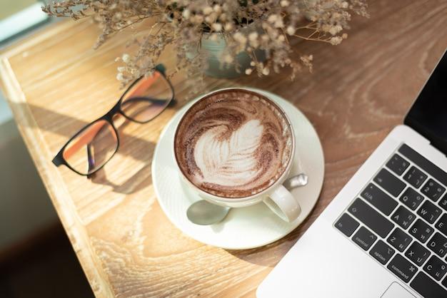 Gorąca kawa latte art, notes i szklanki na stół z drewna w kawiarni Premium Zdjęcia