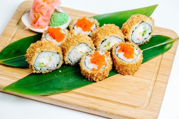Gorące bułki sushi z paluszkami krabowymi, awokado podawane na liściach na desce Darmowe Zdjęcia