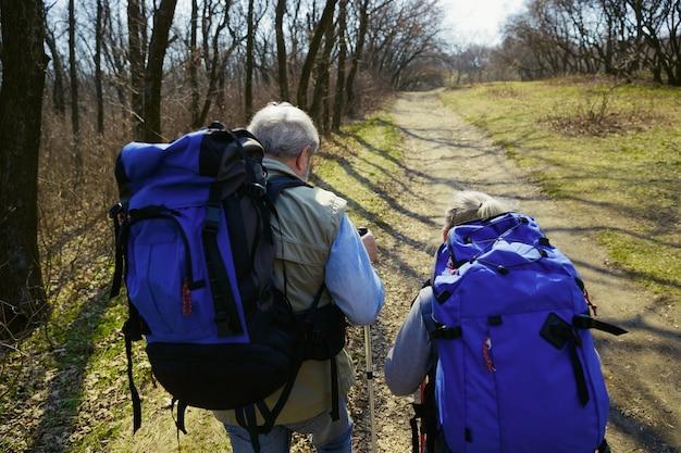 Gotowy Na Więcej. Starsza Rodzina Para Mężczyzna I Kobieta W Strój Turystyczny Spaceru Na Zielonym Trawniku W Pobliżu Drzew W Słoneczny Dzień. Pojęcie Turystyki, Zdrowego Stylu życia, Relaksu I Wspólnoty. Darmowe Zdjęcia