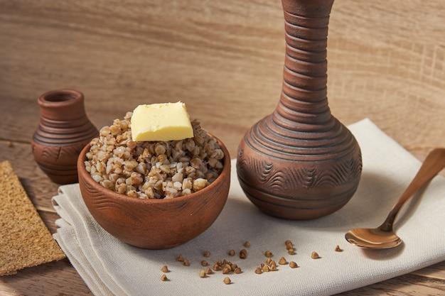 Gotujący Gryczany Zboże W Brown Glinianym Pucharze Na Drewnianym Stole. Bezglutenowe Ziarno Dla Zdrowej Diety Premium Zdjęcia