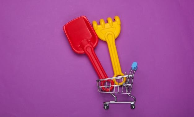 Grabie Dla Dzieci I łopata Do Piaskownicy Lub Plaży W Wózku Na Zakupy Na Fioletowo Premium Zdjęcia