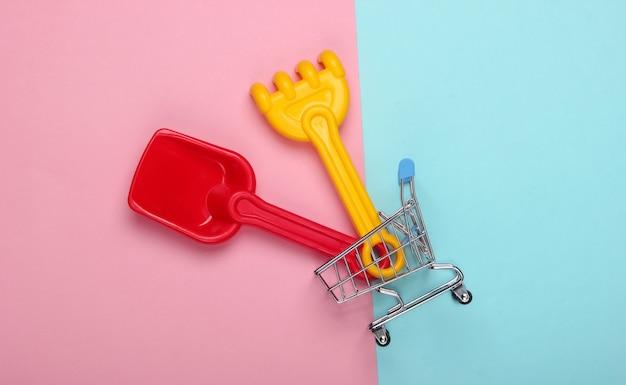 Grabie Dla Dzieci I łopata Do Piaskownicy Lub Plaży W Wózku Sklepowym Na Różowo-niebieskim Pastelu Premium Zdjęcia
