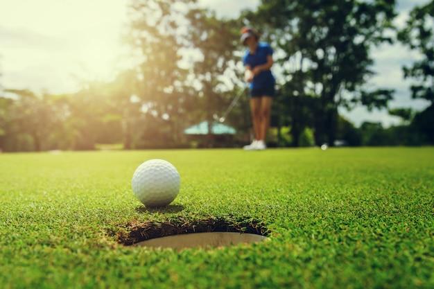 Gracz golfa stawia piłkę golfową w dziurę Premium Zdjęcia