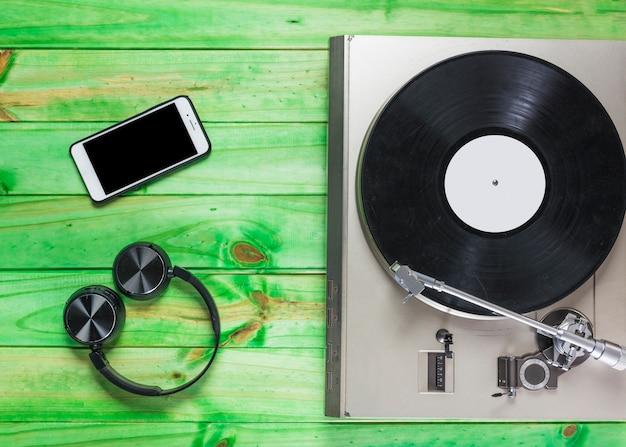 Gramofon winylowy; słuchawki i telefon na zielonym tle drewnianych Darmowe Zdjęcia