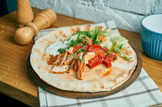 Greckie żyroskopy Z Jogurtem, Kurczakiem, Ogórkiem I Pomidorami Na Drewnianym Stole. Uliczne Jedzenie Premium Zdjęcia