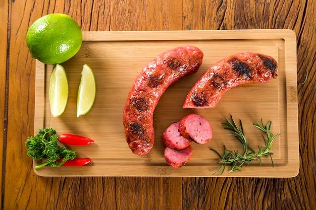Grillowane Kiełbaski Z Grilla Na Desce Z Cytryną, Ziemniakami I Pomidorami Premium Zdjęcia