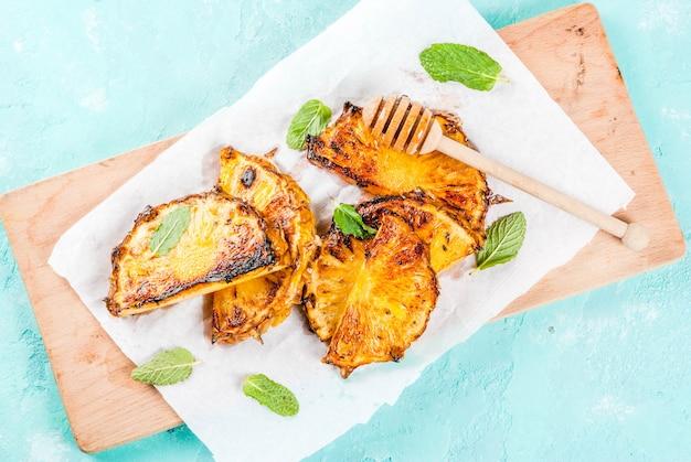 Grillowane plastry ananasa z miętowym sosem miodowo-limonkowym na jasnoniebieskim tle Premium Zdjęcia