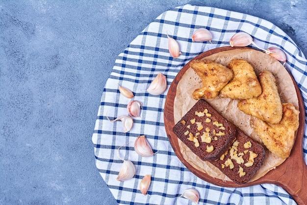 Grillowane Skrzydełka Z Kurczaka Z Czarnym Chlebem Na Desce Na Niebiesko Darmowe Zdjęcia