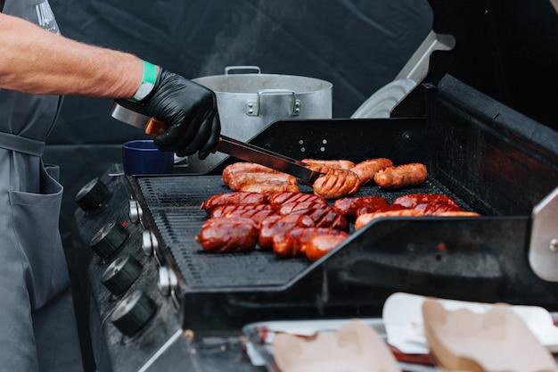Grillowanie Kiełbasek Na Grilla. Grill W Ogrodzie. Festiwal Street Food Premium Zdjęcia