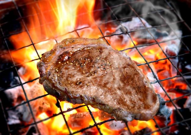 Grillowanie Steków Pieprzowych Na Płonącym Ogniu Premium Zdjęcia