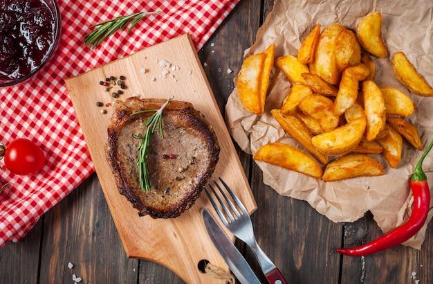 Grillowany Stek Wołowy Doprawiony Przyprawami Podawany Na Drewnianej Desce Ze świeżym Pomidorem Cherry, Pieczonymi Ziemniakami I Czerwoną Ostrą Papryczką Chili. Premium Zdjęcia