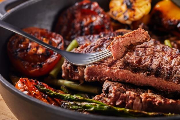 Grillowany Stek Wołowy Na Czarnej Patelni, Kawałek Posiekanego Na Widelcu, Z Pieczonymi Warzywami - Pomidorami, Szparagami, Czosnkiem I Papryką Premium Zdjęcia