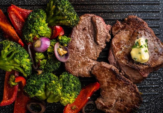 Grillowany Stek Wołowy Z Masłem Czosnkowym I Warzywami. Mięso Z Grillowaną Papryką, Brokułami I Cebulą. Premium Zdjęcia