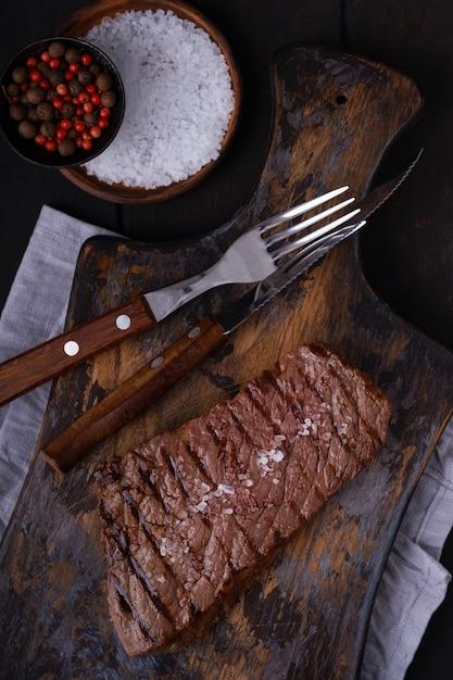 Grillowany Stek Wołowy Z Nożem I Widelcem Na Desce Do Krojenia. Ugotowane Jedzenie Premium Zdjęcia