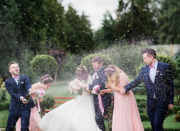 Groomsman Otwiera Butelkę Szampana Przed Nowożeńcami Stojącymi W Parku Premium Zdjęcia