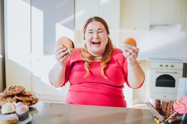 Gruba Młoda Kobieta W Kuchni Siedzi I Jedzenie Fast Foodów. Premium Zdjęcia