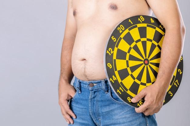 Grubi Ludzie Trzymający Okrągłą żółtą Tarczę Do Rzutek Obok Pozycji Brzucha. Cel Koncepcji Utraty Wagi. Premium Zdjęcia