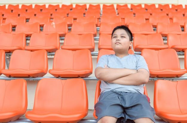 Gruby Chłopiec Siedzi Na Trybunie Piłkarskiej Premium Zdjęcia