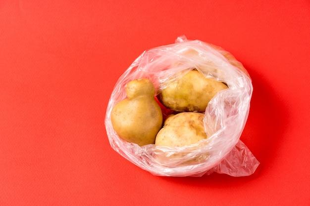Grule w plastikowym worku na czerwonym tle. przestań używać sztucznych toreb do przechowywania żywności. Premium Zdjęcia