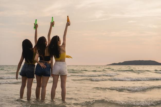 Grupa azjatyckich nastoletnich dziewcząt posiadających party świętuje na plaży Darmowe Zdjęcia
