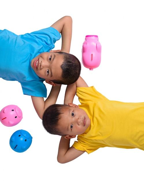Grupa azjatykci dzieci zabawę z prosiątko bankiem odizolowywającym na białym tle Premium Zdjęcia