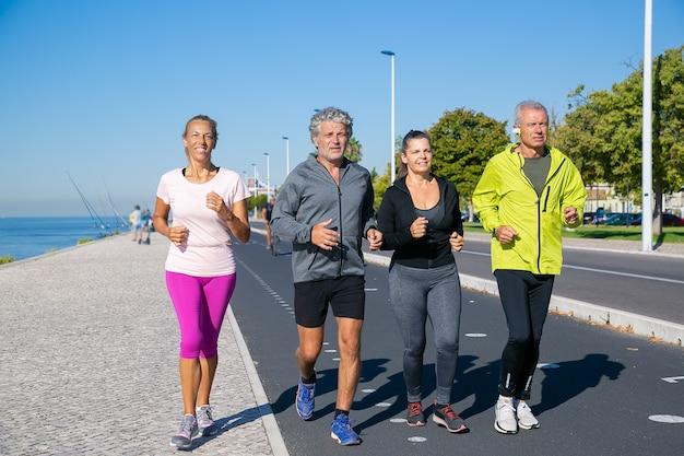 Grupa Dojrzałych Ludzi Ubranych W Sportowe Ubrania, Biegając Wzdłuż Brzegu Rzeki. Ujęcie Pełnej Długości. Koncepcja Emerytury Lub Aktywnego Stylu życia Darmowe Zdjęcia