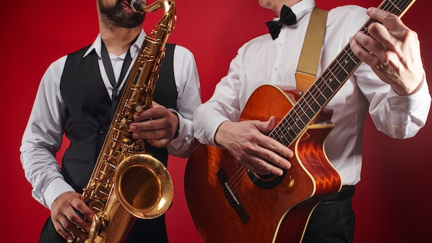 Grupa Dwóch Muzyków, Męskiego Zespołu Jazzowego, Gitarzysty I Saksofonisty W Klasycznych Kostiumach Improwizuje Na Instrumentach Muzycznych W Studio Na Czerwonym Tle Premium Zdjęcia