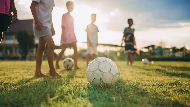 Grupa dzieci bawiących się w piłkę nożną w piłkę nożną do ćwiczeń na wsi Premium Zdjęcia