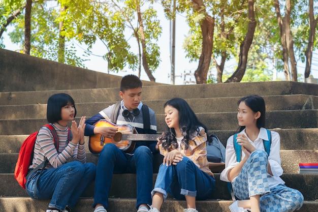 Grupa Dziecko Uczeń Bawić Się Gitarę I śpiewa Piosenki Wpólnie W Lato Parku Premium Zdjęcia