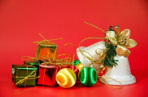 Grupa Dzwon I Prezent W Bożych Narodzeniach Na Czerwonym Tle Premium Zdjęcia