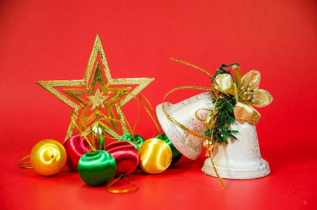 Grupa Dzwon, Piłka I Prezent W Bożych Narodzeniach Na Czerwonym Tle Premium Zdjęcia