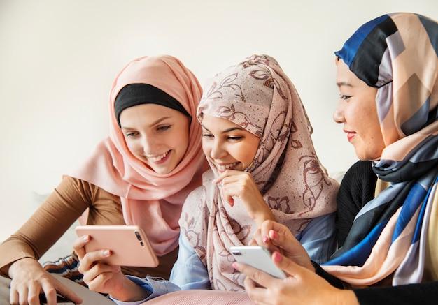 Grupa islamskie kobiety opowiada wpólnie i ogląda na telefonie Premium Zdjęcia