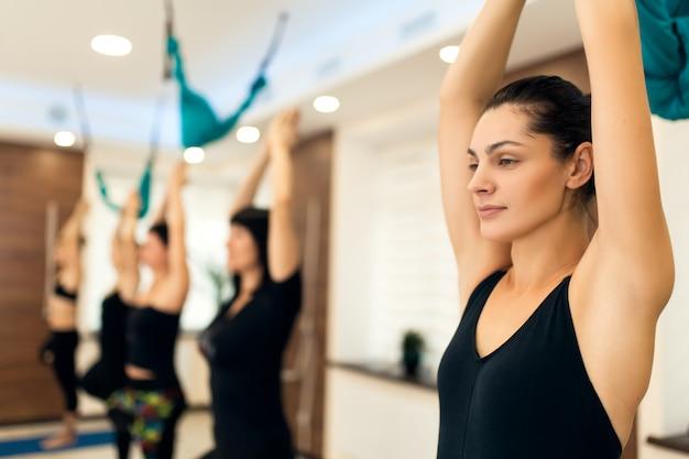 Grupa kobiet robi ćwiczenia jogi w siłowni Premium Zdjęcia