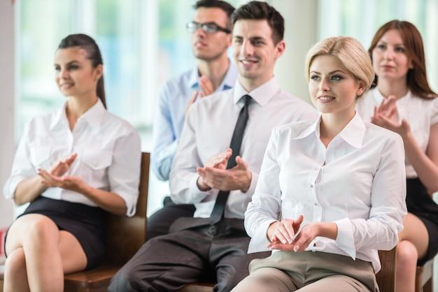 Grupa ludzi klaskanie w ręce podczas spotkania. Premium Zdjęcia