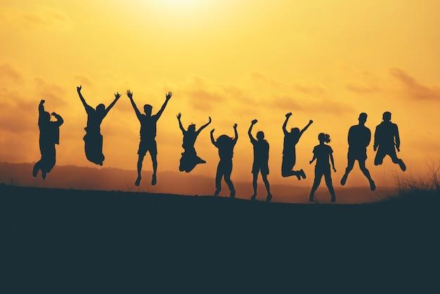 Grupa ludzi skacze nad halnym zmierzchem, przyjaciela przyjęcie, szczęśliwy czas Premium Zdjęcia