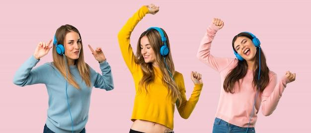 Grupa ludzi z kolorowymi ubraniami słucha muzyka z hełmofonami Premium Zdjęcia