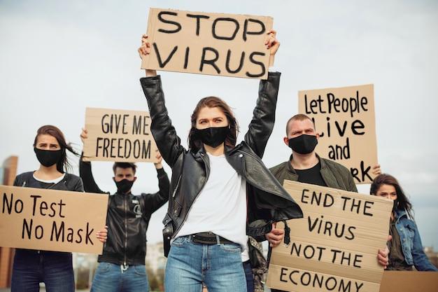 Grupa Ludzi Z Maską I Plakatami, Którzy Protestują Przeciwko Spotkaniu Z Plakatami, Zatrzymuje Fałszywego Wirusa Premium Zdjęcia