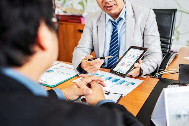 Grupa męscy przedsiębiorcy dyskutuje zarządzanie projekt podczas pracować wpólnie Premium Zdjęcia