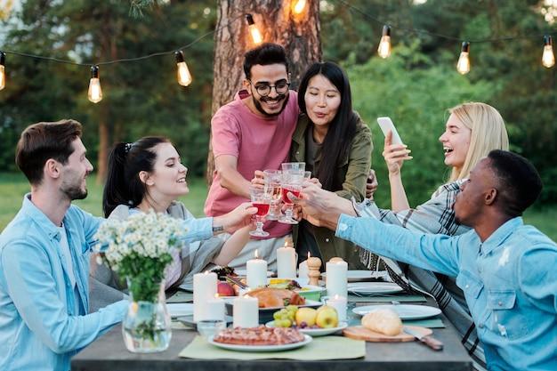 Grupa Międzykulturowych Wesołych Przyjaciół Zebranych Przy Stole Pod Drzewem, Brzęczących Kieliszkami Z Domowym Winem Premium Zdjęcia